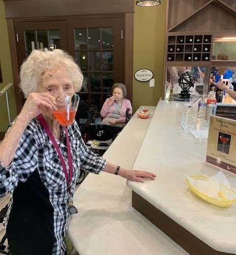 Resident of Chartwell Oakville Retirement Residence enjoying an Astor Martini