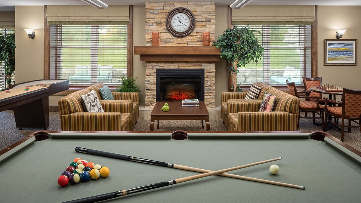 Common area with billiards table and fireplace at Chartwell Montgomery Village retirement residence