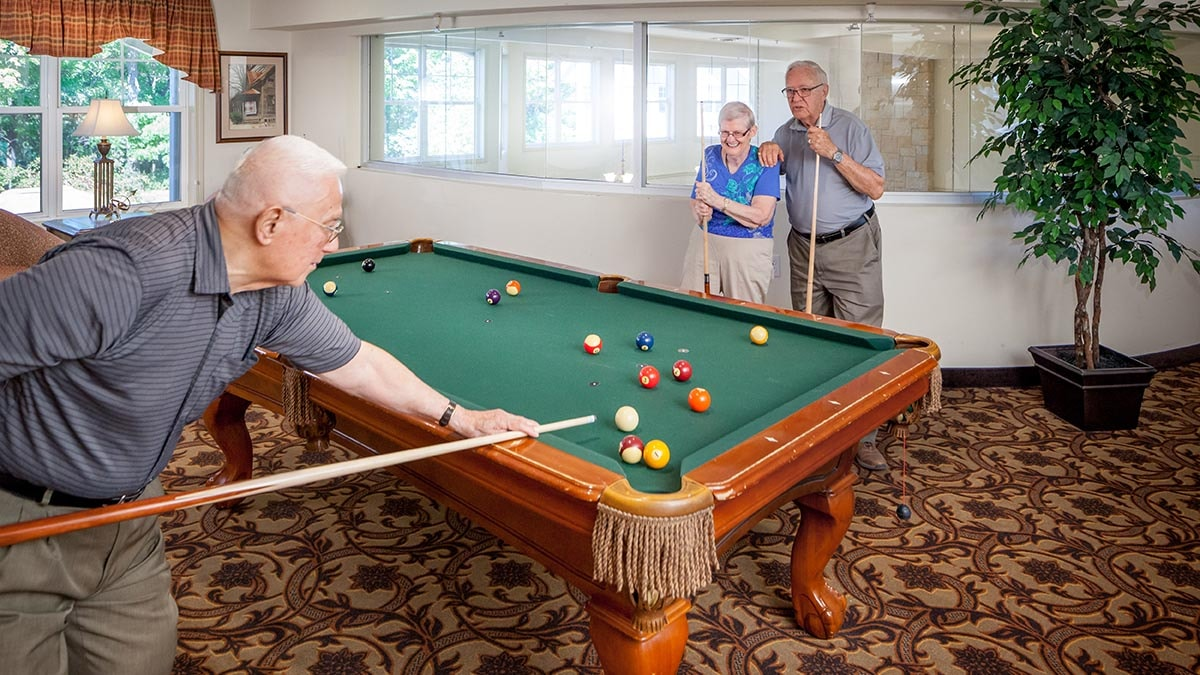 residents playing pool at Chartwell Rouge Valley Retirement Residence