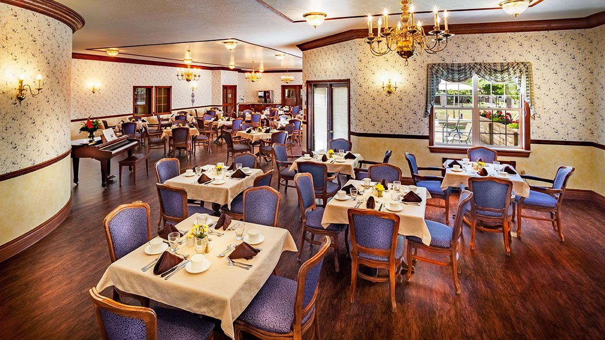 Large dining room with beautiful wooden floors in Chartwell Anne Hathaway retirement residence