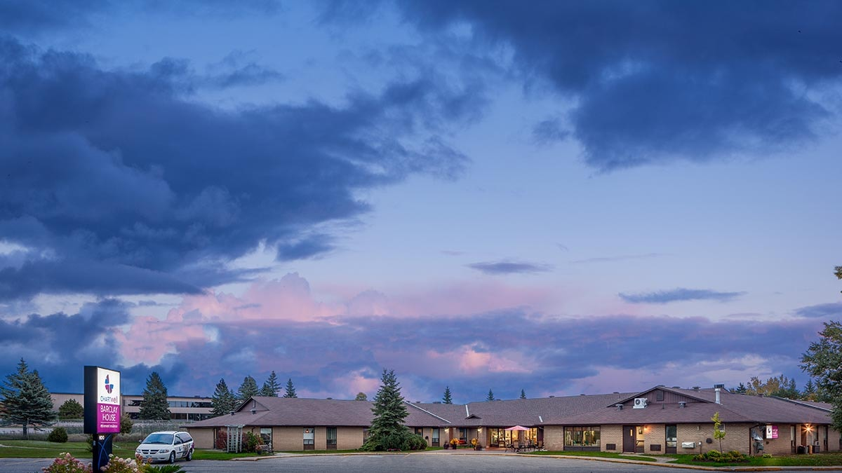 Breathtaking exterior photo of Chartwell Barclay House retirement residence at dusk with beautiful clouds