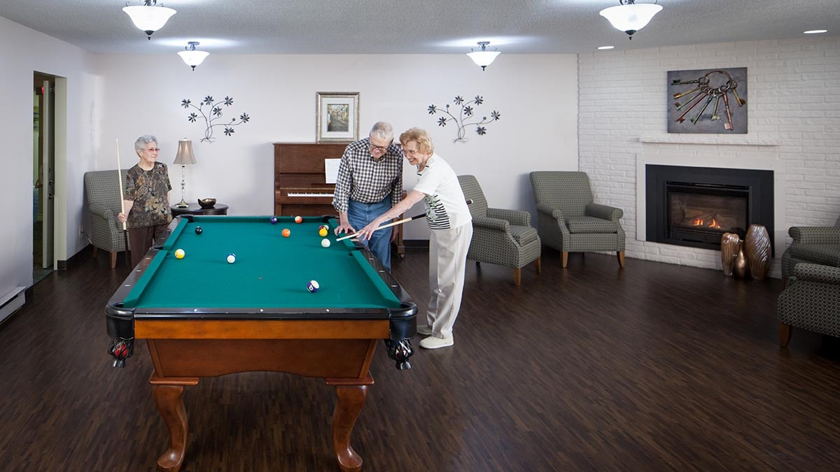 Residents playing pool at Chartwell Barclay House retirement residence