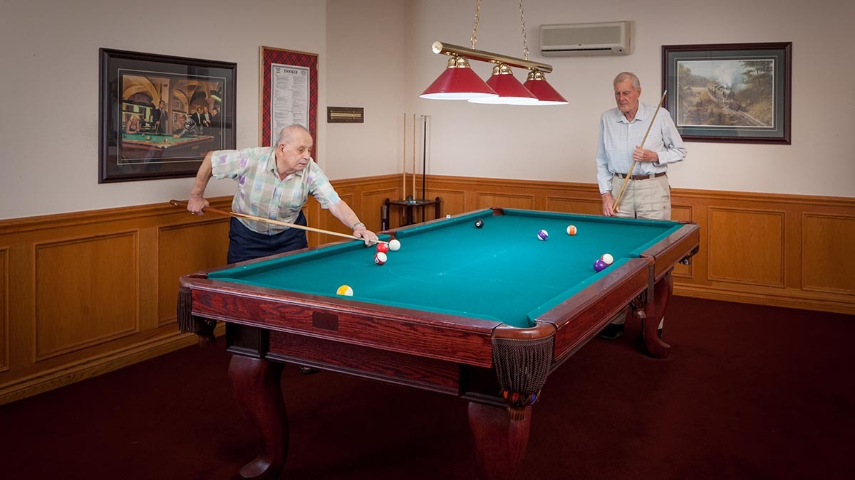 Gentleman playing billiards at Chartwell Barton Retirement Residence